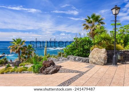 Promenade and tropical flowers along ocean in Puerto de la Cruz, Tenerife, Canary Islands, Spain - stock photo