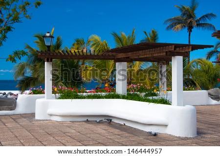 Promenade with palm tree garden in Puerto de la Cruz near Lago Martianez, Tenerife, Canary Islands, Spain - stock photo