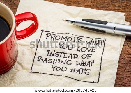 Promote what you love instead of bashing what you hate - handwriting on a napkin with cup of coffee - stock photo
