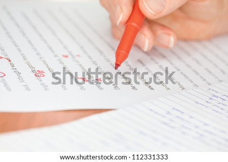 Proofreader with red pen checks a transcribed page  - stock photo