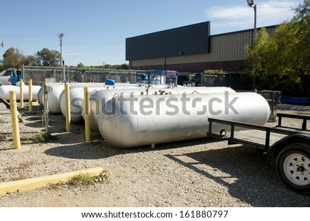Propane tanks wait for transport beside a flatbed trailer. - stock photo