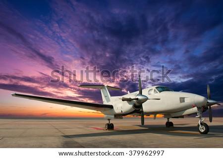 Propeller plane parking at twilight - stock photo