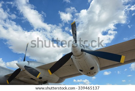 propellers of airplane flying in blue sky with clouds  - stock photo
