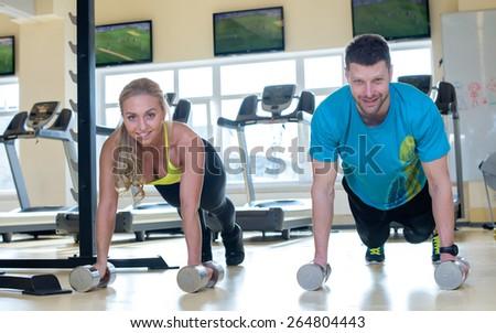 Proper sport shape. Two sportsmen, male and female, are having intensive training in a gym. Both are using dumbbells in a workout. Perfect shape. - stock photo