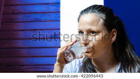 Property daily water intake - close up portrait of pretty girl drinking the water from glass - stock photo