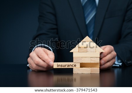 Property (family house) insurance protection concept. Insurance agent complete wooden model of the house with last piece with text insurance.  - stock photo