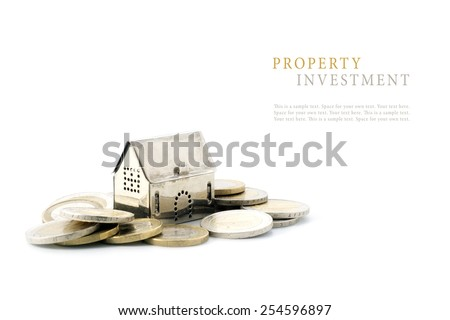 property investment, silver golden house model on coins isolated on white background, copy space with sample text - stock photo