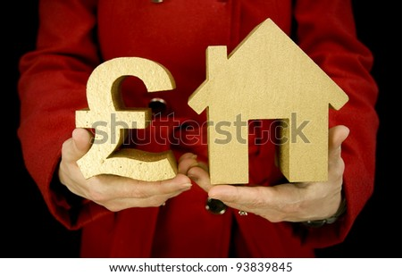 property purchase, woman holding golden house and a golden pound symbol - stock photo