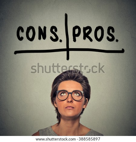 pros and cons, for and against argument concept. Young business woman with glasses looking up deciding isolated on gray wall background. Face expression, emotion, feeling, perception, vision, decision - stock photo