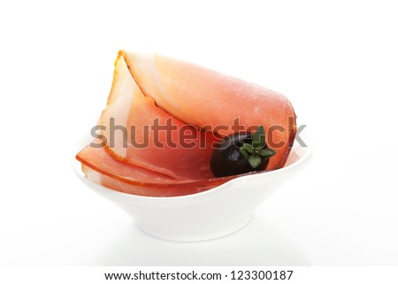 Prosciutto canape with black olive and fresh rosemary herb isolated on white background. Culinary luxurious gastronomy. - stock photo