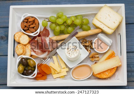 prosciutto, cheese with cookies, grape and nuts - stock photo