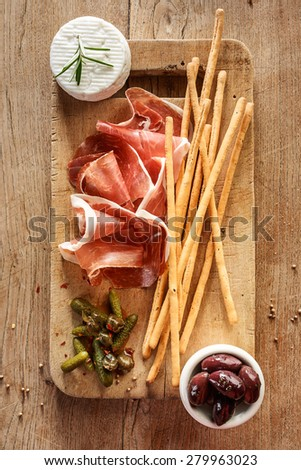 Prosciutto di parma with grissini, olives, capers and goat cheese. Traditional Italian ham - stock photo