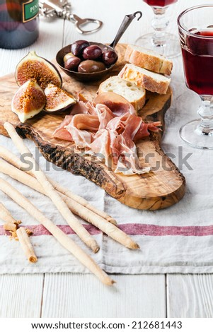 Prosciutto ham and Olives on olive wood cutting board - stock photo