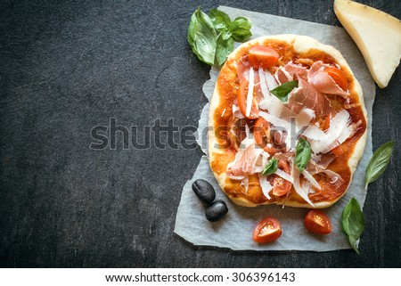 Prosciutto mini pizza on dark background with blank space for your ads  - stock photo