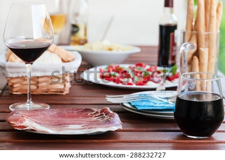 Prosciutto, red wine, mozzarella an tomatoes served on wooden table at balcony. - stock photo