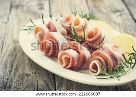 Prosciutto with rosemary on a white plate, toned - stock photo