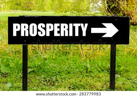 PROSPERITY written on directional black metal sign with arrow pointing to the right against natural green background. Concept image with available copy space - stock photo