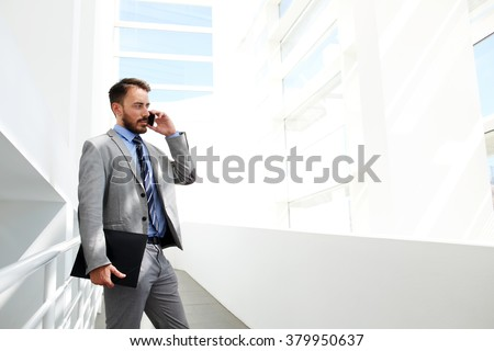 Prosperous businessman having mobile phone conversation before meeting with new specialists, young skilled male architect phoning via cell telephone while standing in office interior near copy space - stock photo