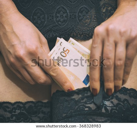 Prostitute hiding money in her stockings. Close-up view. - stock photo