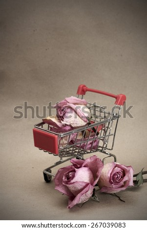Prostitution concept. Dried roses in pushcart, on dirty brown background - stock photo