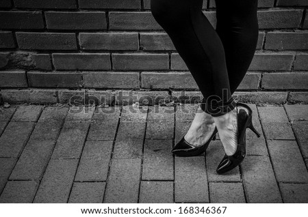 prostitution, prostitute standing against a wall on sidewalk with copy space - stock photo