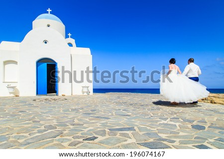 PROTARAS - MAY 2: Young couple on their way to the white chapel near the sea May 2, 2014 In Protaras, Greece. Holidays on a Greek island very often is a great occasion for exotic wedding ceremony. - stock photo