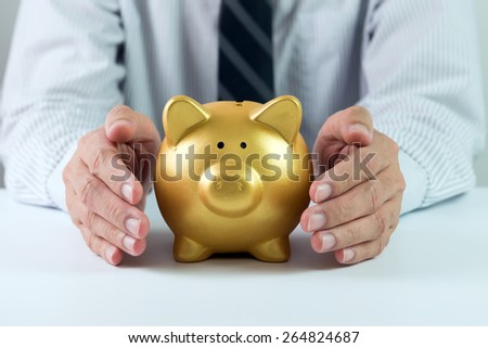 Protect your saving concept using hands covering golden piggy bank - stock photo