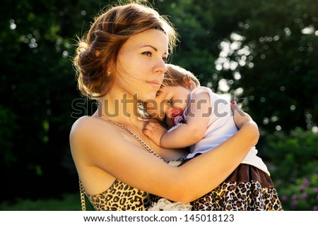 Protection, a mother hugs a child at sunset - stock photo