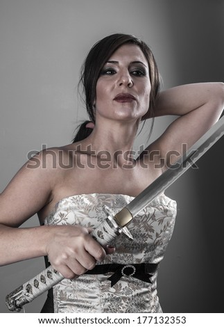 Protection.Anime stylized brunette with short hair holding a katana sword with two hands - stock photo