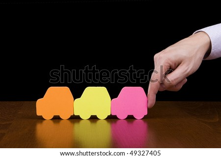 Protection concept - Finger pushing / helping a line of colorful cars - stock photo