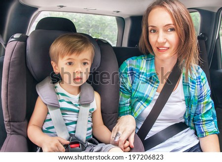 Protection in the car. Caucasian cute son and mother are buckled with safety belt in a car.  Little boy is sitting in the car seat. Woman takes care about kid. Vehicle and transportation concept. - stock photo
