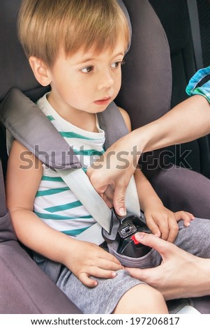 Protection in the car. Hands of caucasian woman is fastening security belt to happy child, who is sitting in safety car seat (chair). Little toddler has a trip. Vehicle and transportation concept.  - stock photo