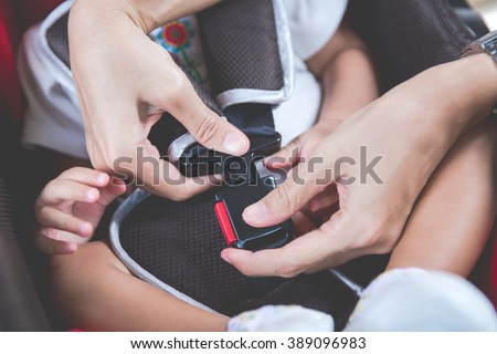 Protection in the car. Hands of  woman is fastening security belt to baby in car seat - stock photo