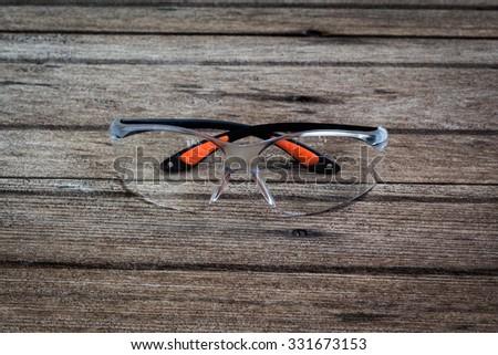 Protective Eyewear / Safety Glasses Isolated on wood background - stock photo