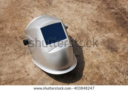 Protective welding mask helmet on outdoor floor with shallow depth of field - stock photo