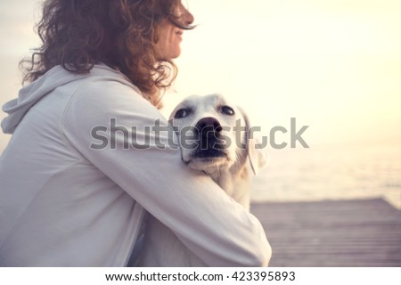 Protective woman embracing his dog while looking the view - stock photo