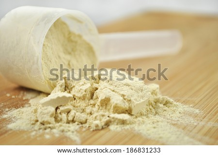 Protein powder or weight loss powder spilling out of a measuring scoop.  - stock photo