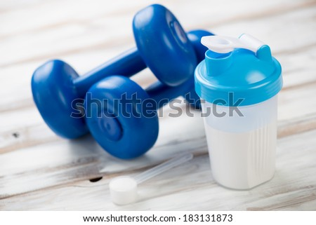 Protein shake and plastic dumbbells on a wooden surface - stock photo