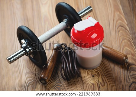 Protein shake with a dumbbell and a jumping rope, studio shot - stock photo