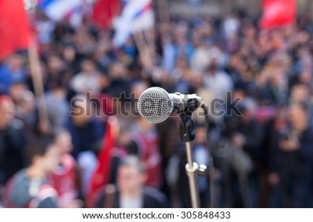 Protest. Public demonstration. Microphone in focus against blurred audience. - stock photo