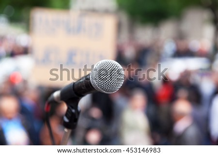 Protest. Public demonstration. Microphone in focus against blurred crowd. Political rally. - stock photo