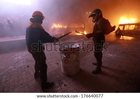 Protesters banging sticks on the barrel. Kyiv, Ukraine, January 19, 2014 - stock photo