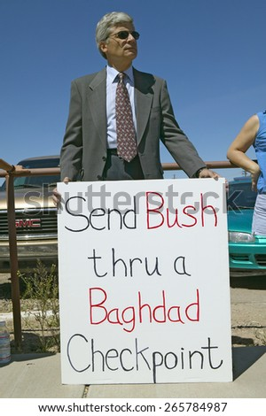 Protestor in Tucson Arizona of President George W. Bush holding a sign protesting his Iraq foreign policy  - stock photo