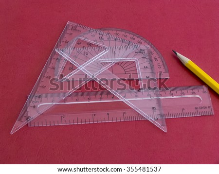 Protractor, rulers and pencil on red background. - stock photo