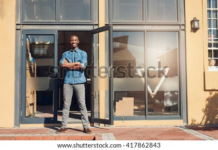 Proud African designer store owner standing in front of shop - stock photo