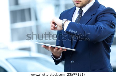Proud Businessman look at clock in front of his office - stock photo