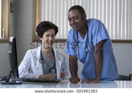 Proud Caucasian female doctor and African American male nurse - stock photo