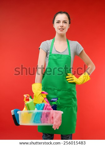 proud caucasian woman standing and holding cleaning supplies against red background - stock photo