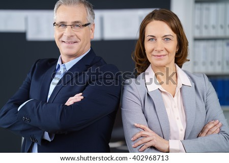 Proud confident mature business partners, a stylish man and woman, standing back to back with folded arms smiling at the camera, office environment - stock photo