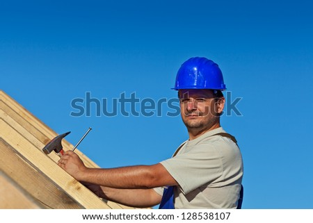 Proud construction worker on the roof structure with nail and hammer - stock photo